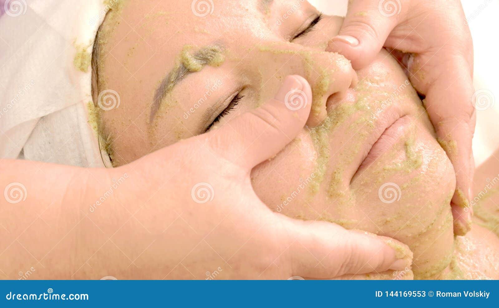 Ręki beautician naciera maskę kiwi ziarna w dziewczyny twarzy Azjatycka kobieta bierze piękno traktowania Pojęcie kosmetologia