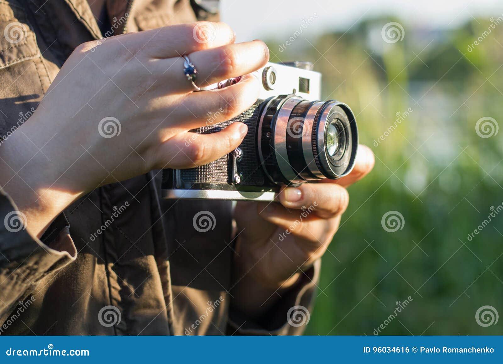 Ręki dziewczyna trzyma rocznik kamerę na tle wysoka zielona trawa