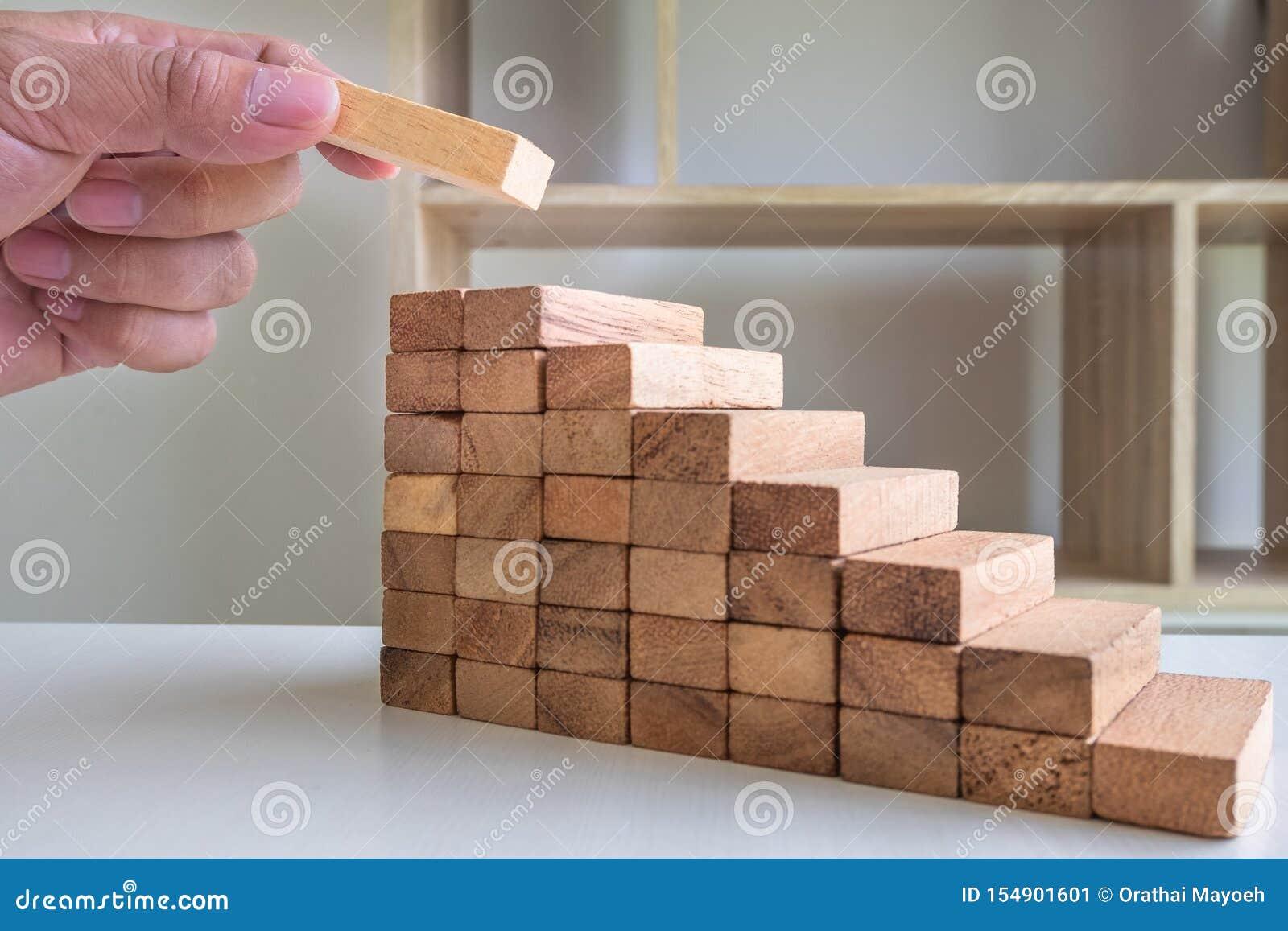 Ręki kładzenia bloki drewniani na narastającym w górę drewna wierza, ryzyka zarządzanie i strategia planu,