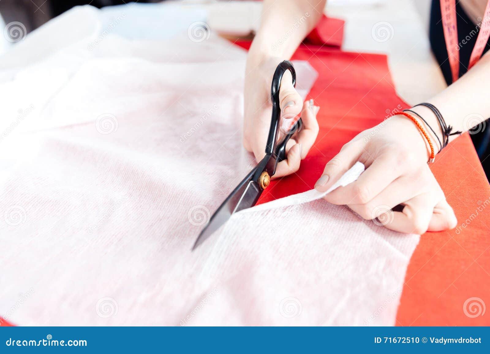 Ręki kobiety szwaczka ciie tkaninę z nożycami