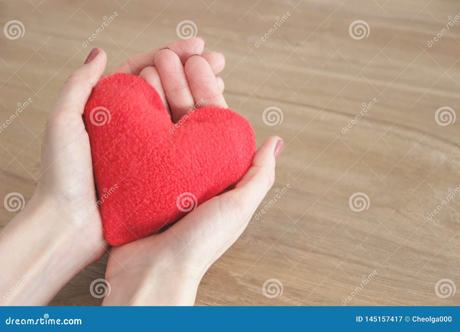 Ręki młoda piękna kobieta delikatnie trzyma czerwonego serce na drewnianym tle, selekcyjna ostrość oprócz przestrzeni,