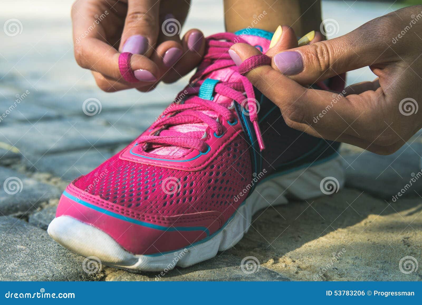 Ręki młodej kobiety sznurowania sneakers