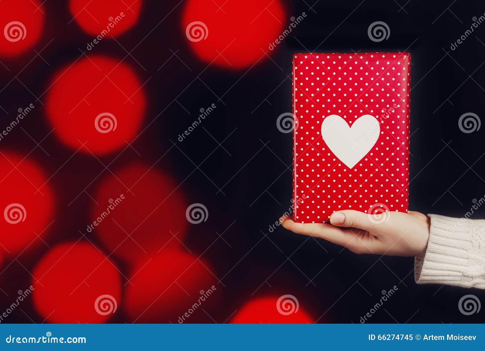 Ręki mienia czerwony prezent odizolowywający na czerni