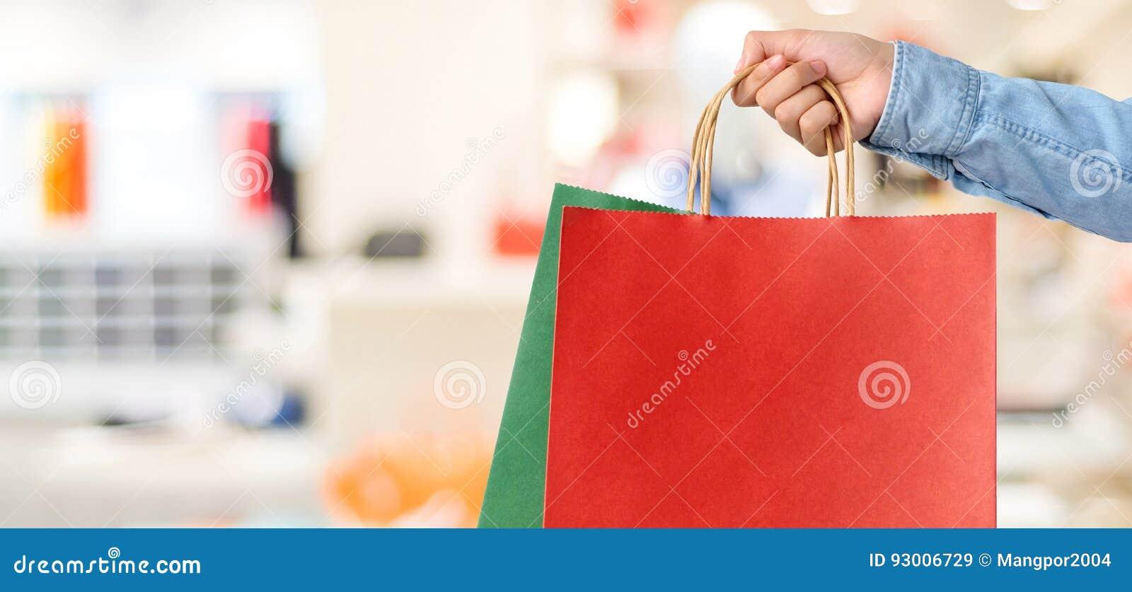 Ręki mienia czerwony torba na zakupy na plama sklepu tle, sztandar w