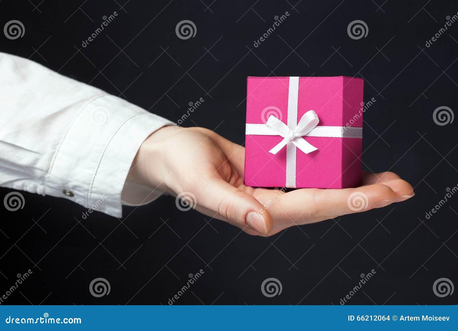 Ręki mienia pudełko dla prezenta odizolowywającego na czerni