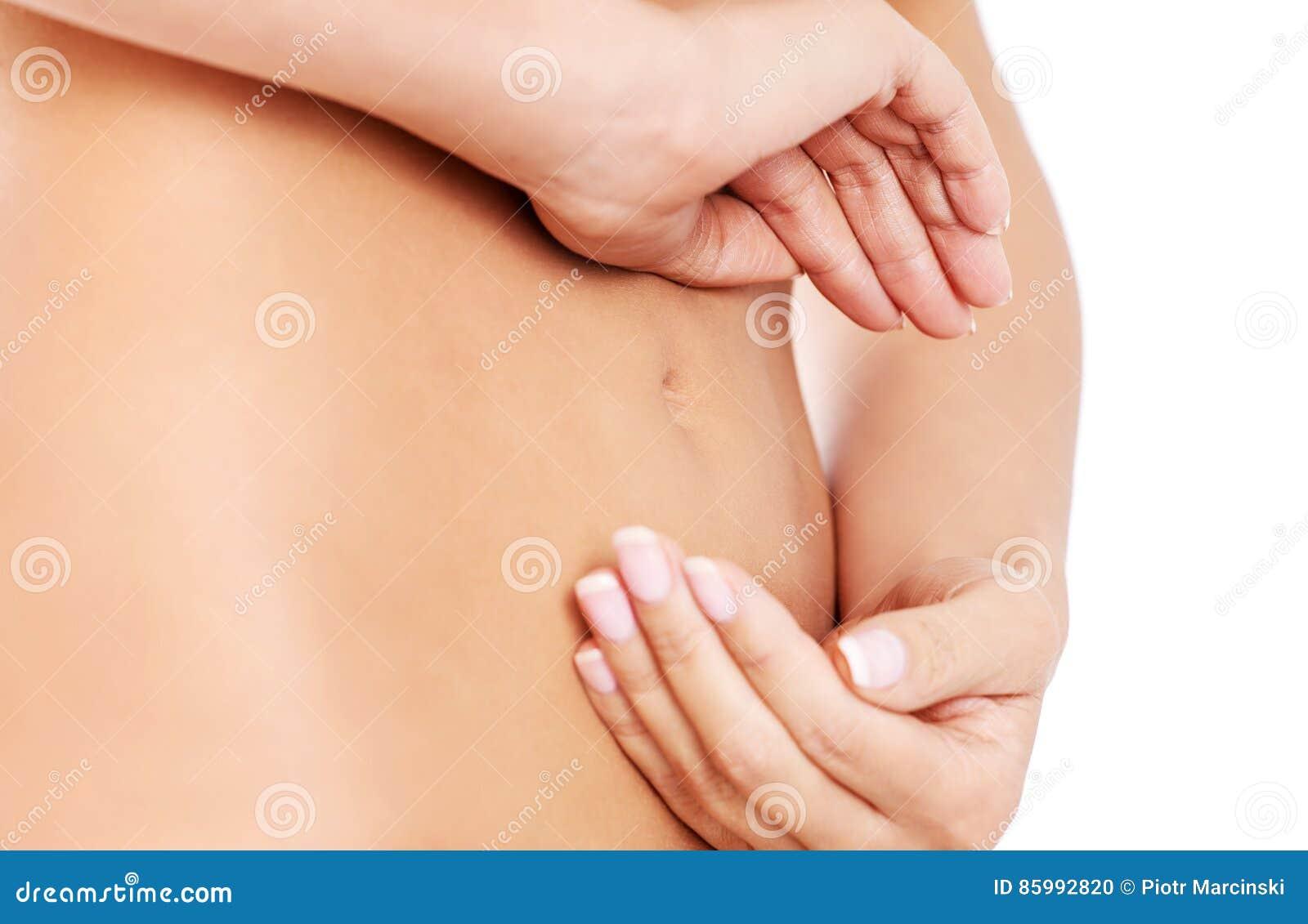 Ręki na szczupłym żeńskim brzuchu