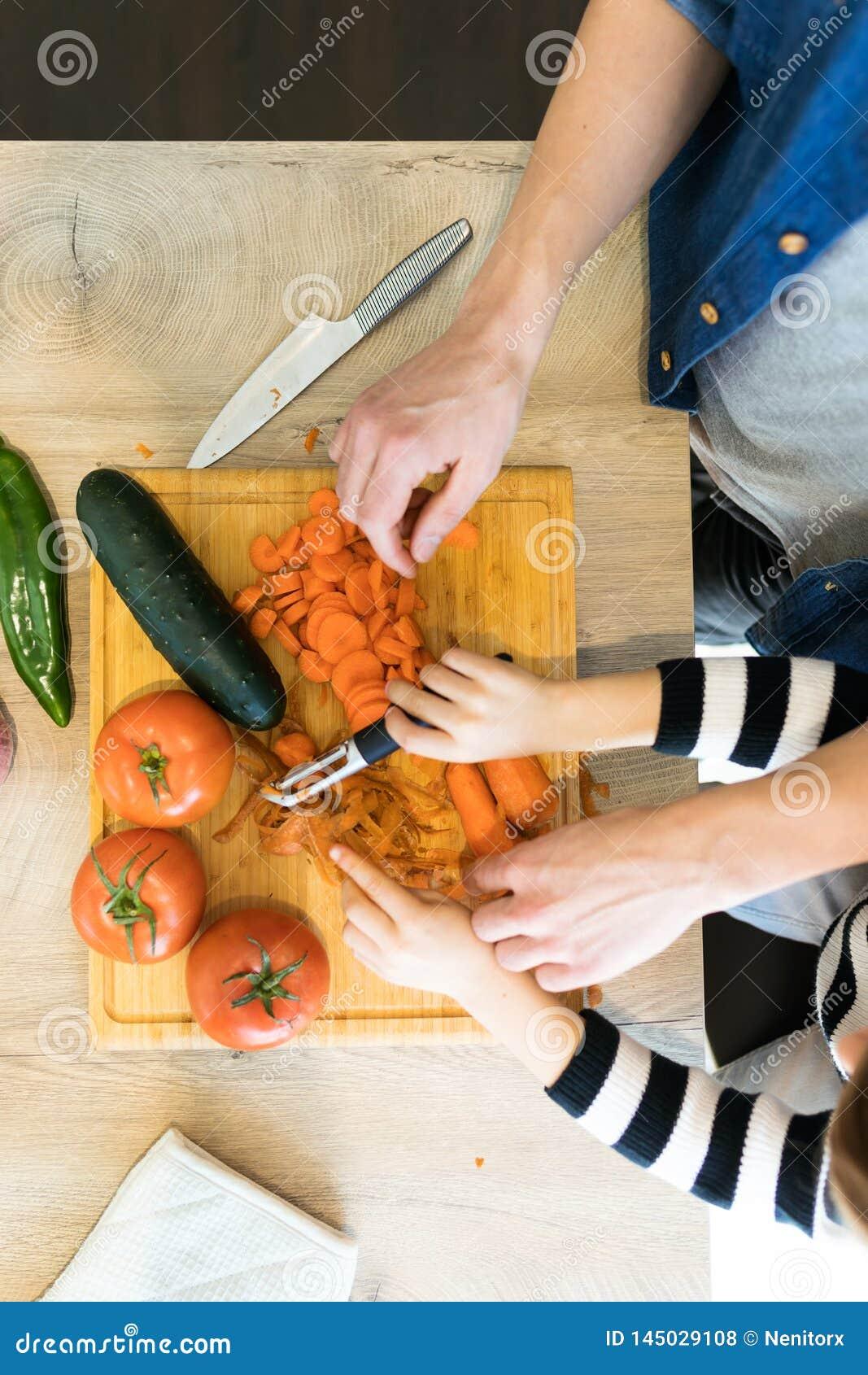 Ręki ojciec i jego syn ciie niektóre warzywa w drewnianym stole w kuchni w domu