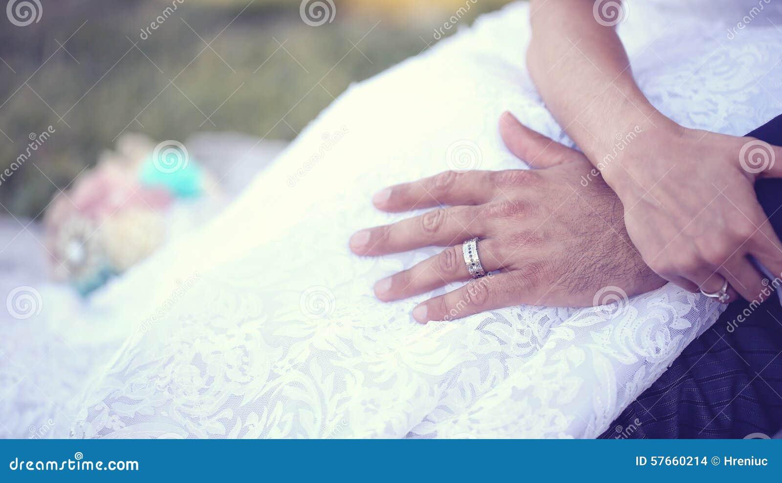 Ręki państwo młodzi jest ubranym obrączki ślubne
