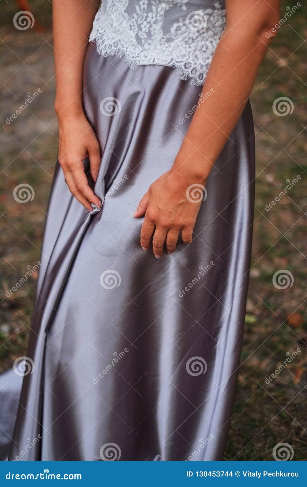 Ręki panny młodej kłamstwo na jedwabniczej purpurze ubierają