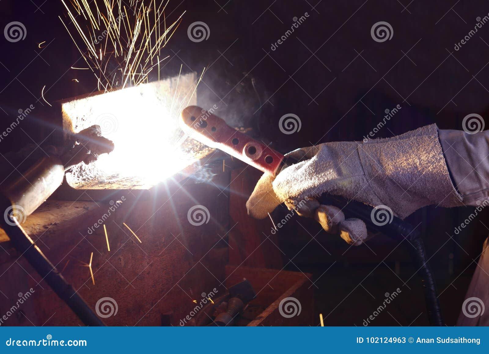 Ręki przemysłowy pracownik z pochodnia metalu spawalniczą stalą z iskrze w warsztacie