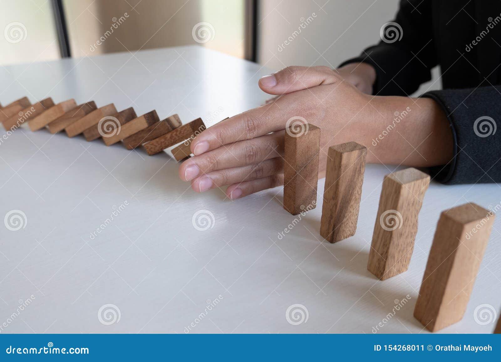 Ręki przerwa blokuje drewnianą grę, uprawia hazard umieszczający drewnianego blok Pojęcia ryzyko zarządzanie i strategia planujem