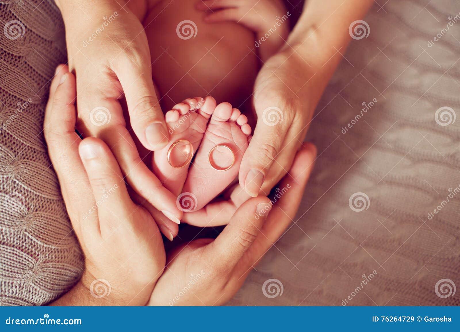 Ręki rodzice trzyma cieki dziecko bystre pierścienie się tło białe
