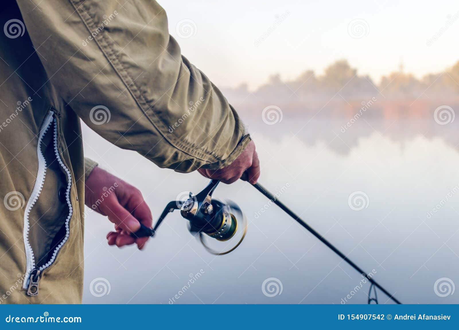Ręki rybak z przędzalnianego prącia i zwitki lata rankiem na jeziorze
