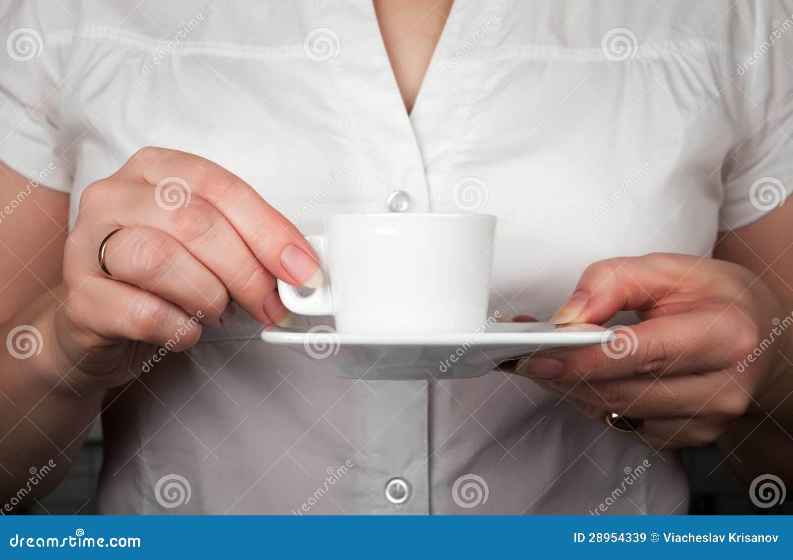 Ręki trzyma filiżankę z kawowymi fasolami