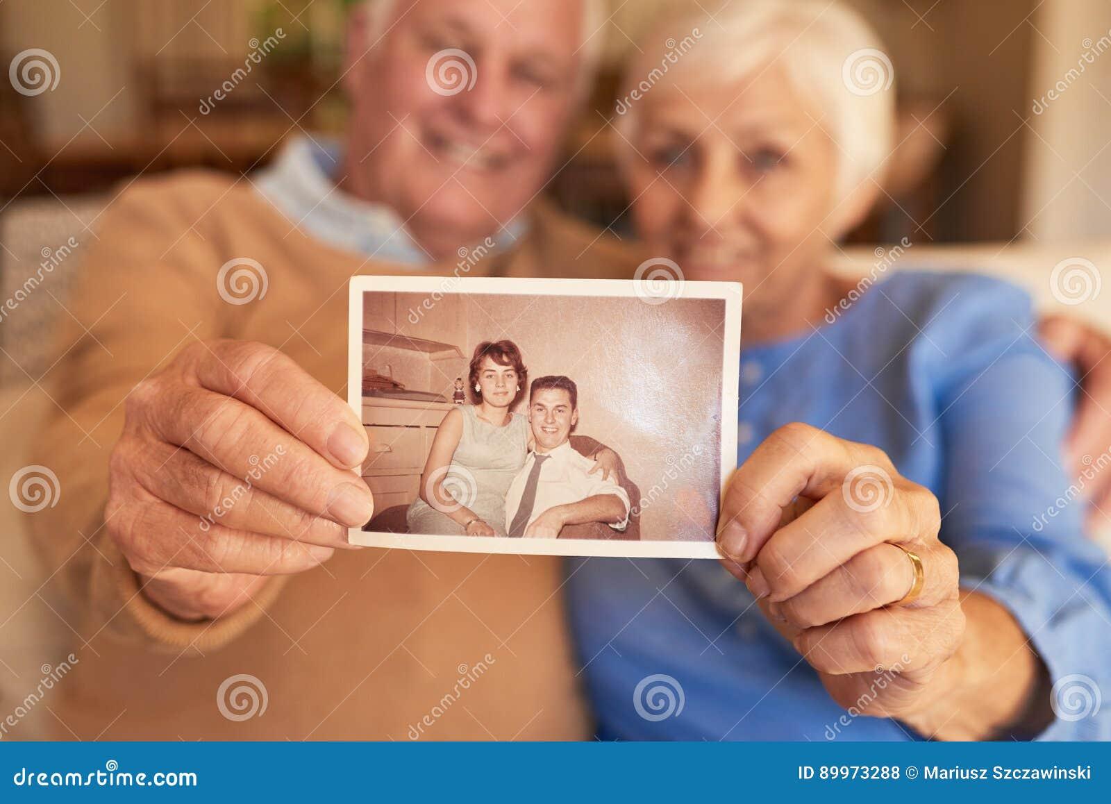 Ręki trzyma ich młodocianą fotografię w domu starsza para