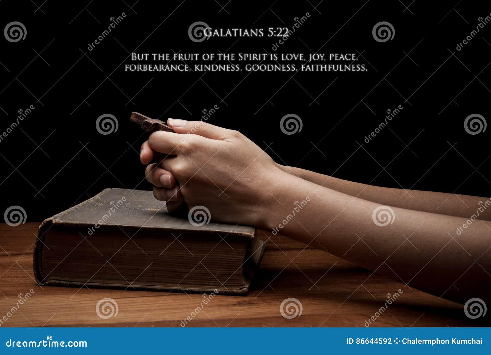 Ręki trzyma krzyż na świętej biblii z wersetem