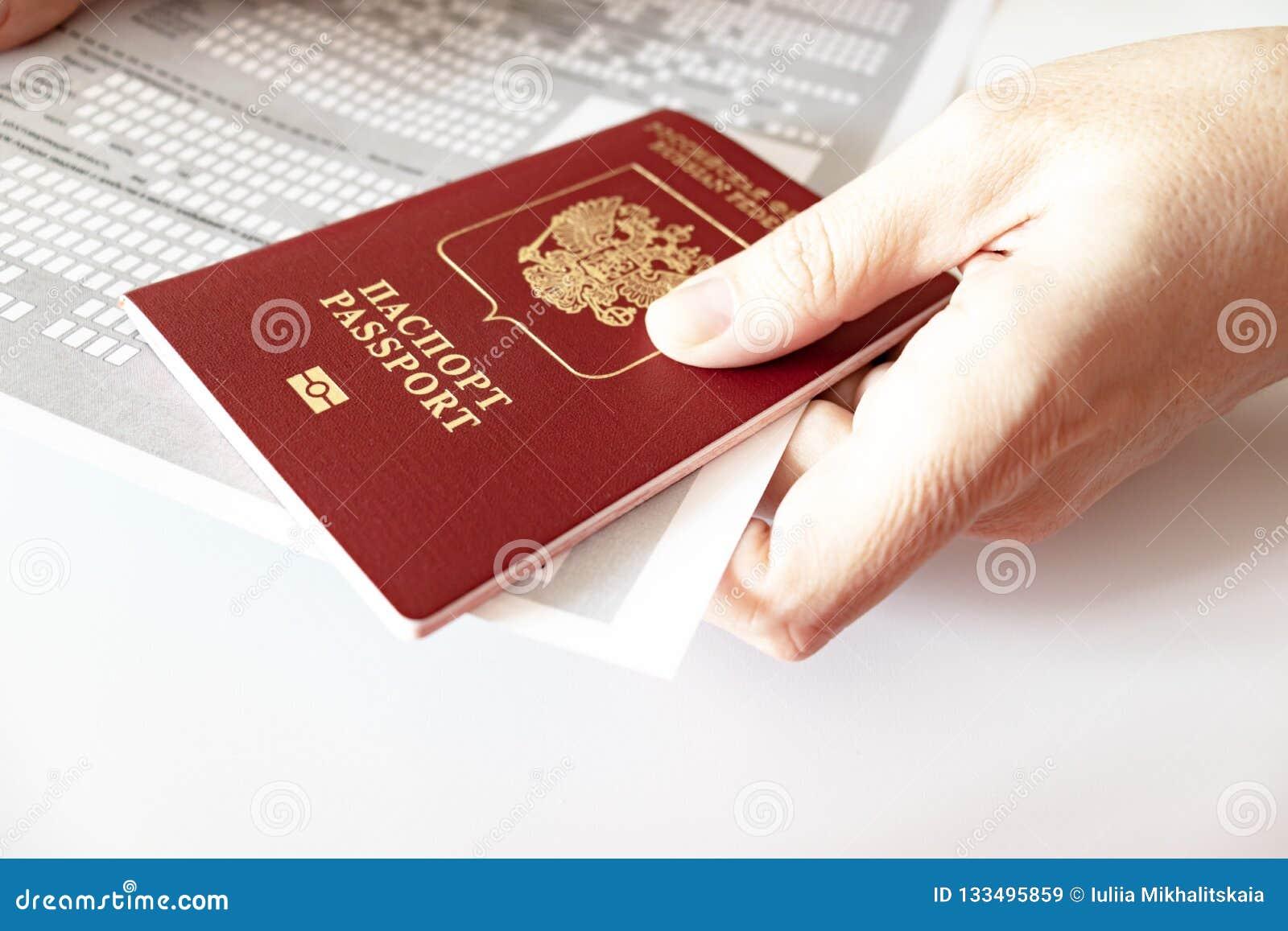 Ręki trzyma rosyjskiego paszport i rejestrację przy miejscem pobyt tworzą