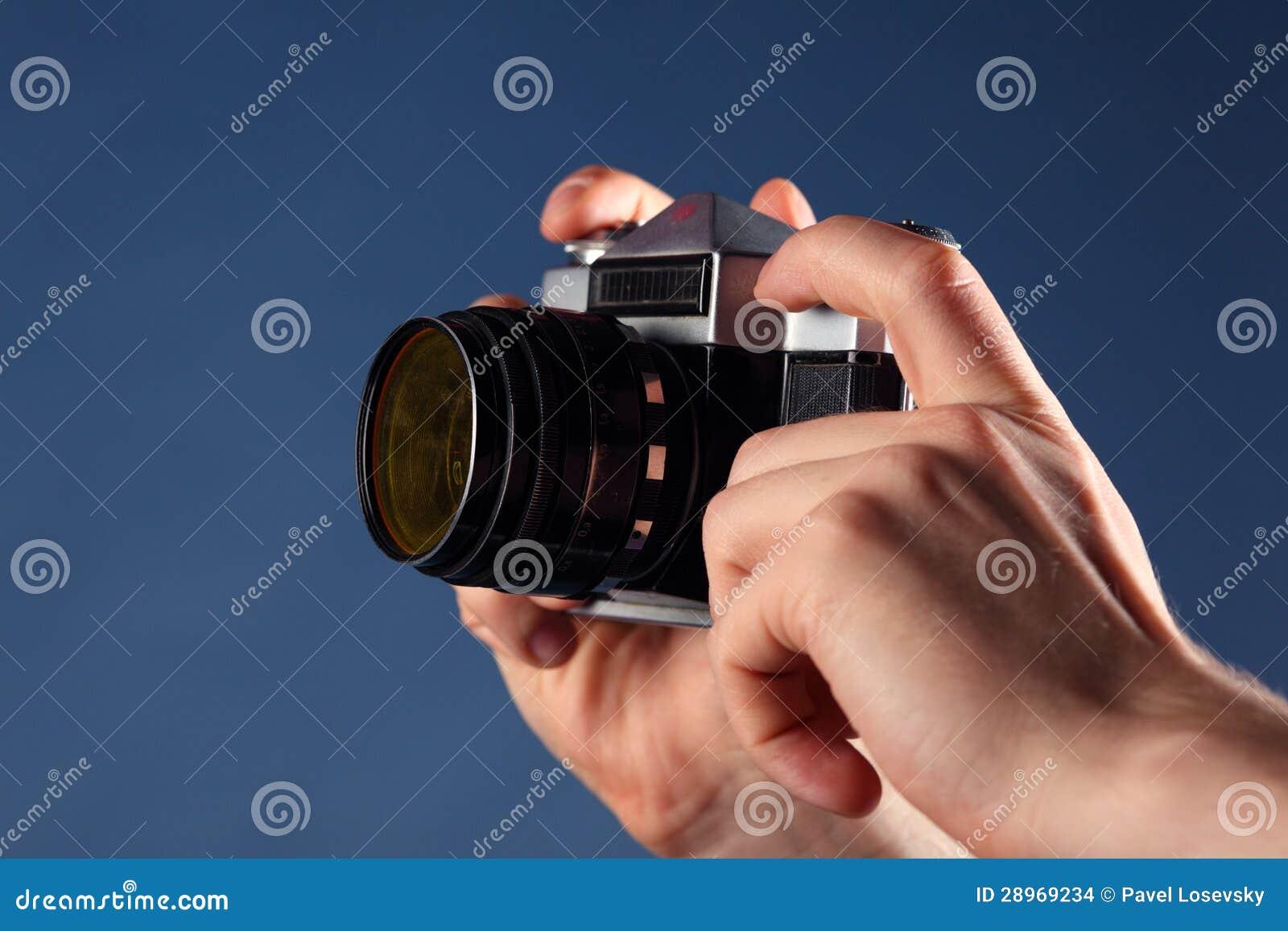Ręki trzymają małą starą kamerę