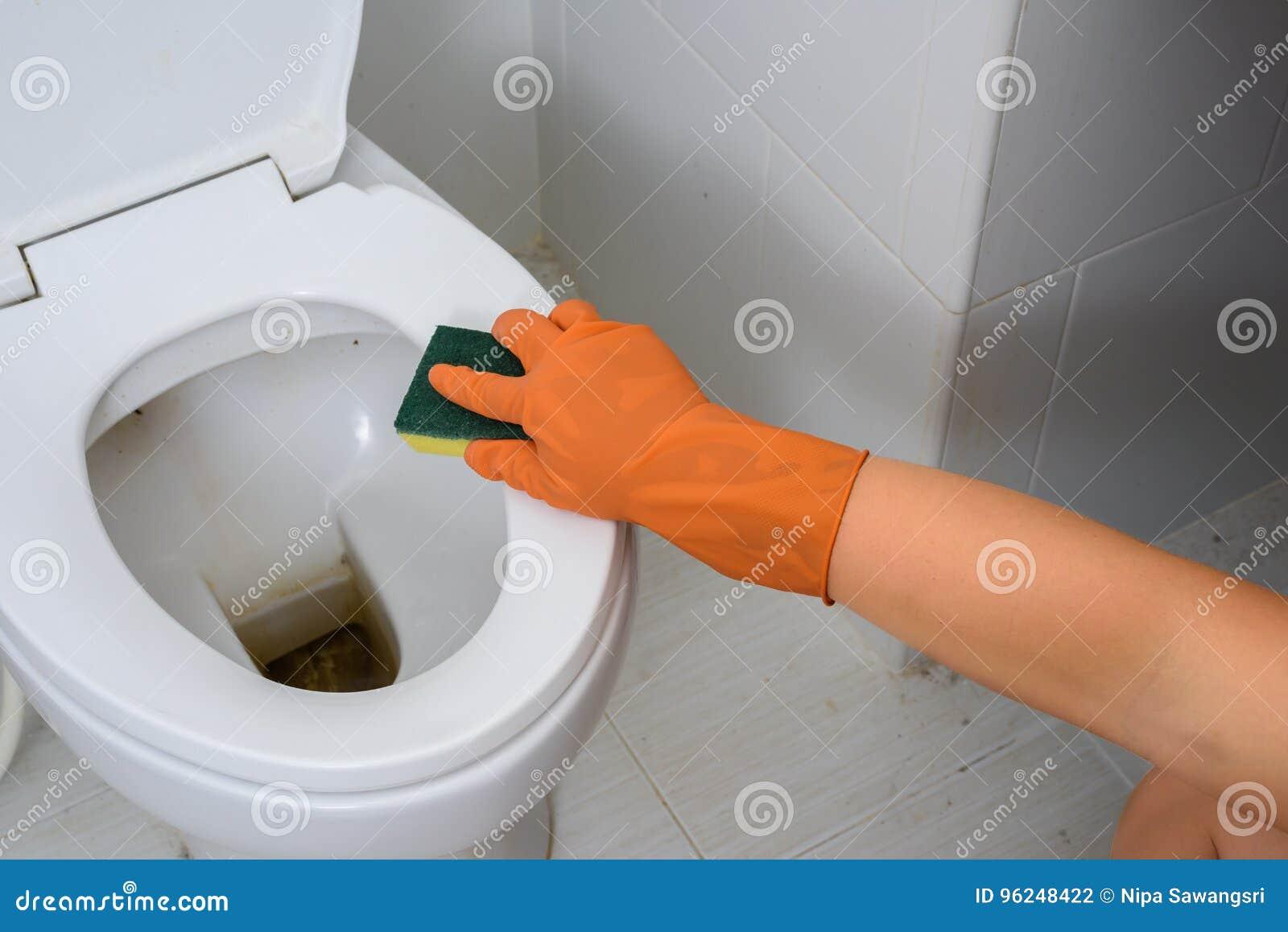 Ręki w Pomarańczowych rękawiczkach czyści WC, toaleta, klozet