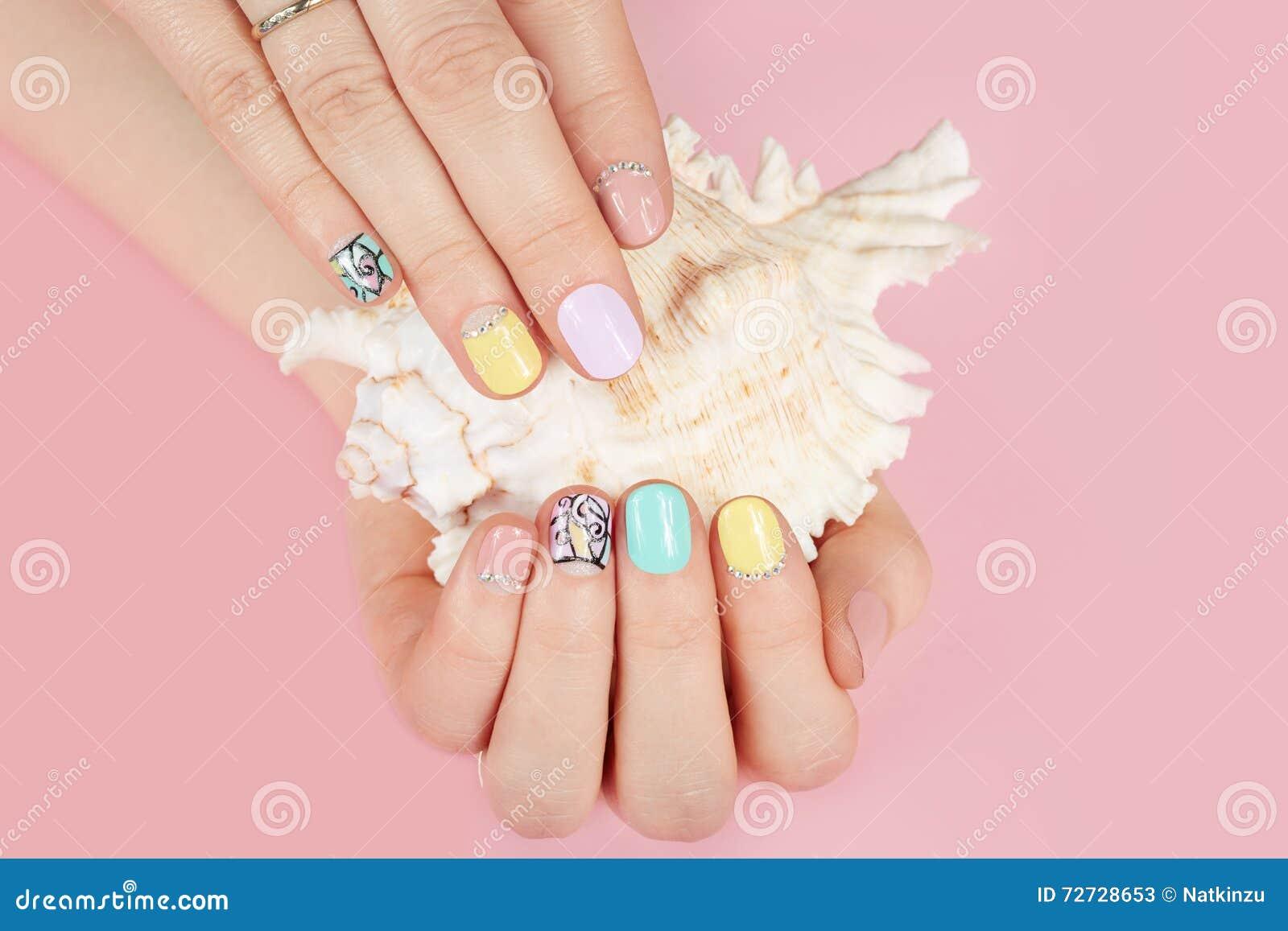 Ręki z pięknymi robiącymi manikiur gwoździami i denną skorupą