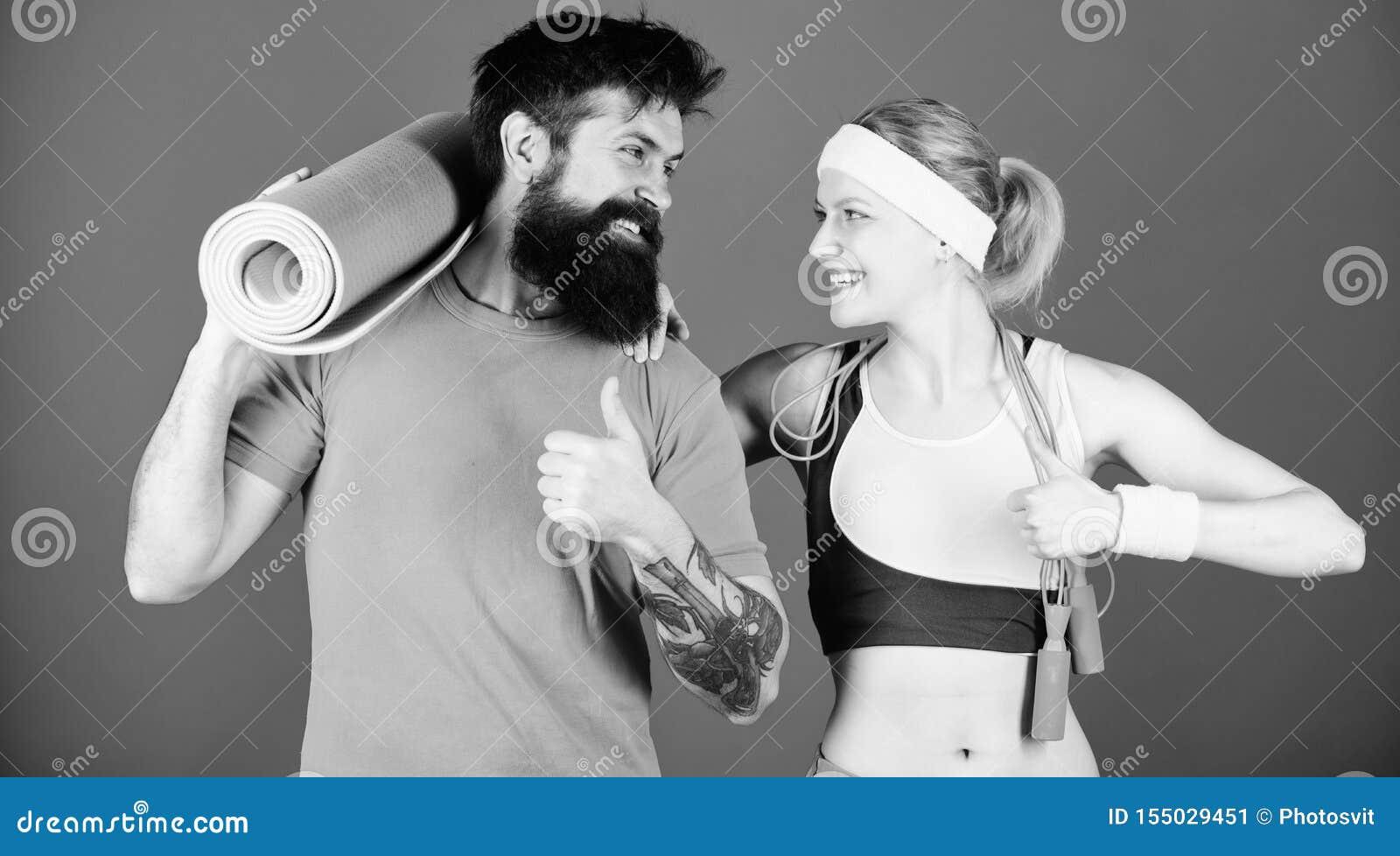 R Άνδρας και γυναίκα με το χαλί γιόγκας και τον αθλητικό εξοπλισμό Ασκήσεις ικανότητας Workout και ικανότητα r