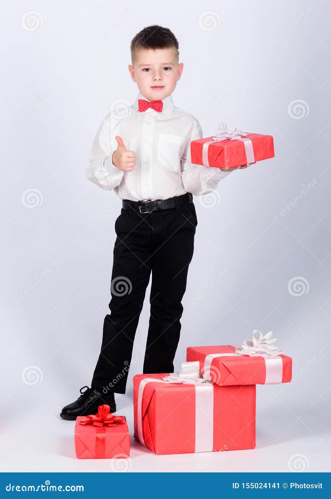 R μικρό παιδί με το δώρο ημέρας βαλεντίνων E Επόμενη μέρα των Χριστουγέννων Νέο έτος ύφος σμόκιν E