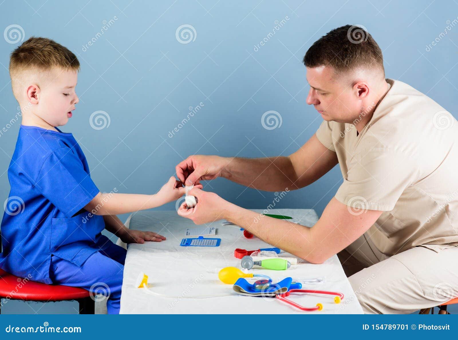 R Ο γιατρός ατόμων κάθεται τα επιτραπέζια ιατρικά εργαλεία εξετάζοντας τον ασθενή μικρών παιδιών Έννοια παιδιάτρων (