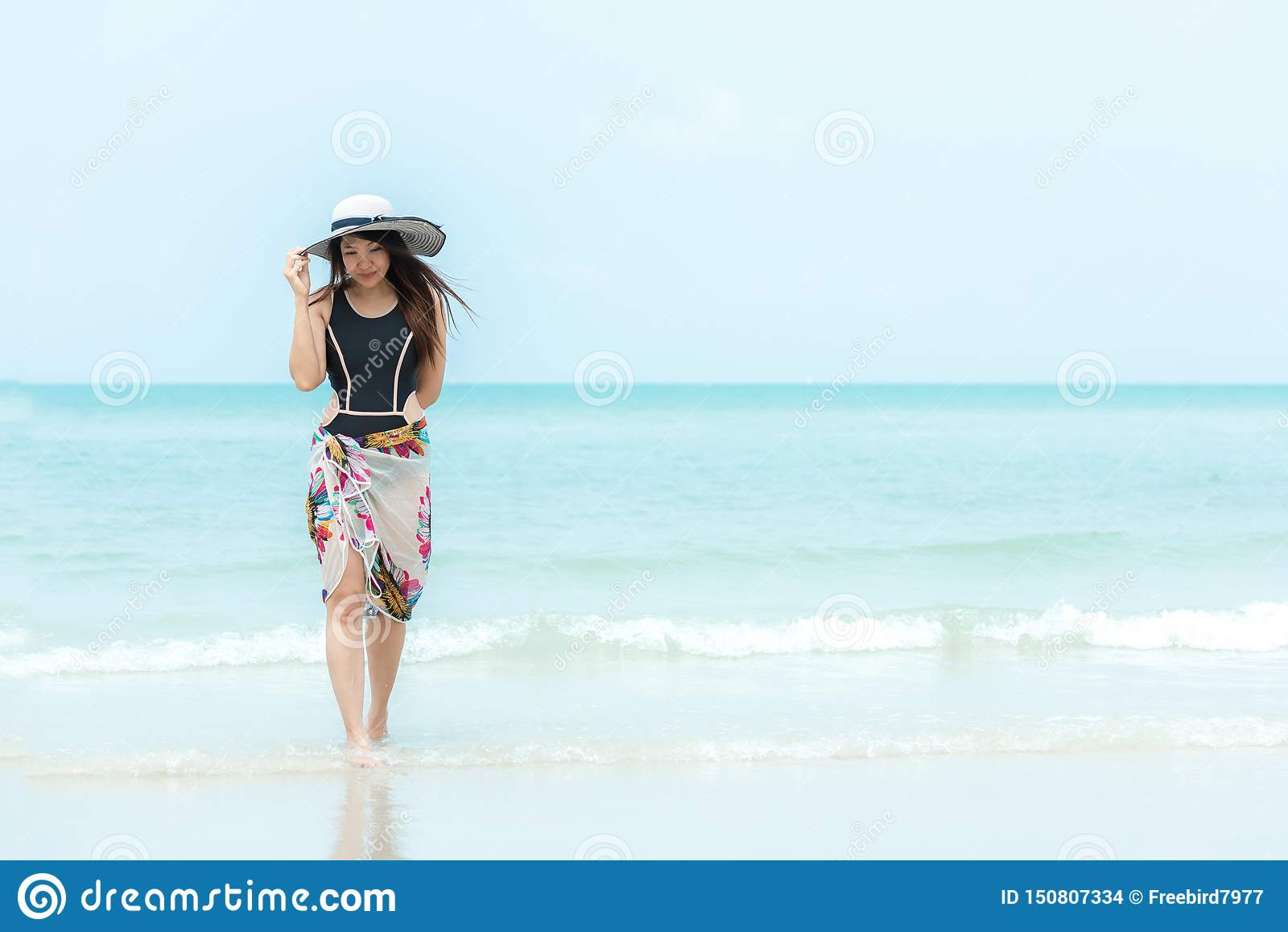 R Ψύχρα γυναικών τρόπου ζωής που κρατά το μεγάλο άσπρο καπέλο και που φορά τα θερινά ταξίδια μόδας μπικινιών που περπατούν στο αμ