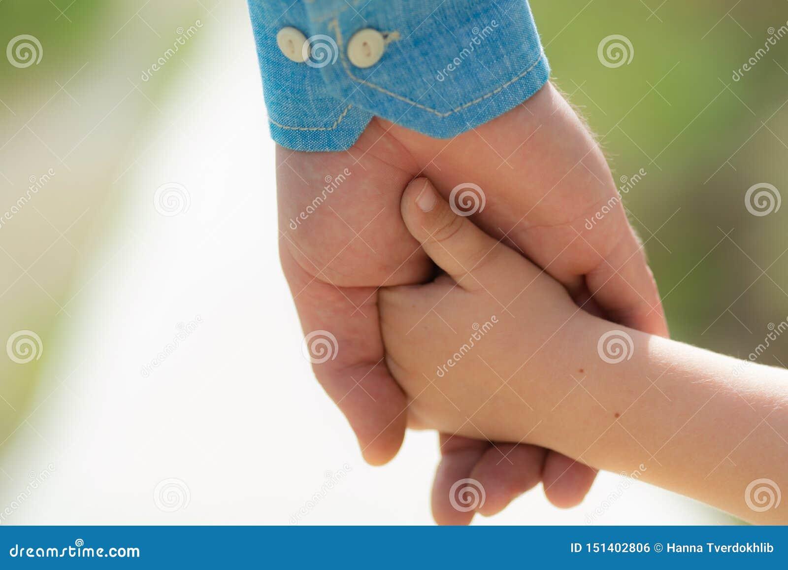 R Маленький ребенок держа руки с его отцом outdoors, крупный план r Крупный план 2 касаясь рук