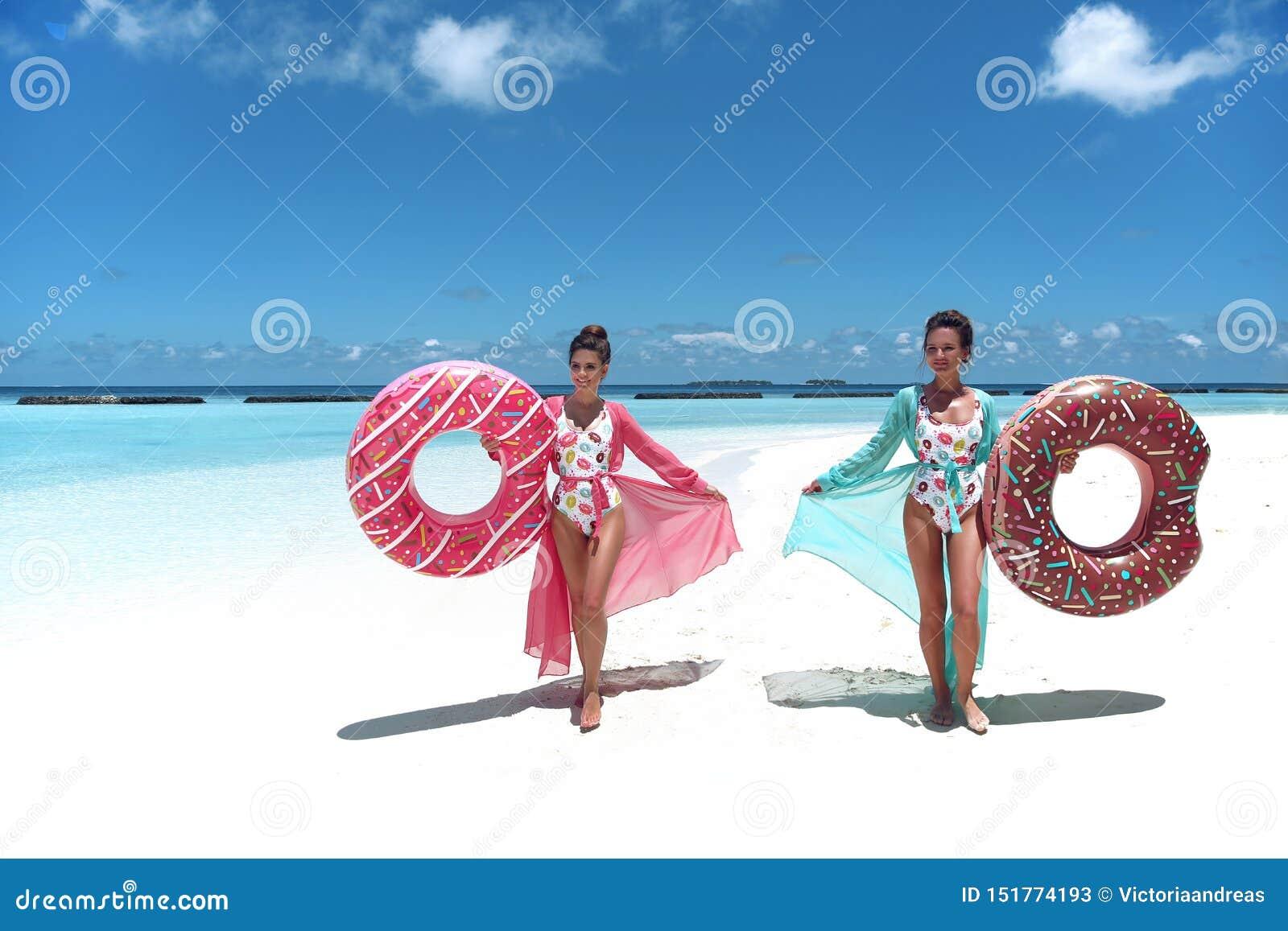 R Счастливые свободные 2 женщины с раздувным тюфяком поплавка донута Девушки нося шифоновый наслаждаться платья пляжа экзотически