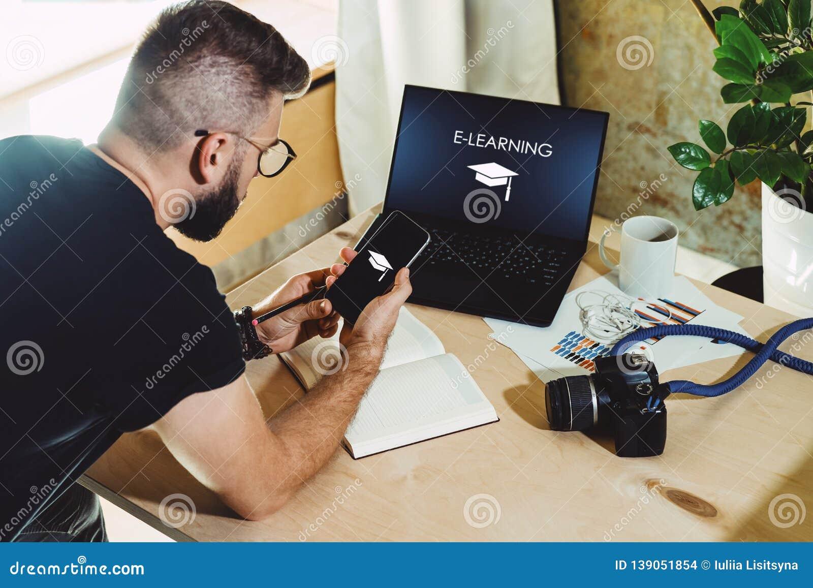 R 人坐家在桌上,研究有题字电子教学的计算机在显示器 人观看webinar在膝上型计算机
