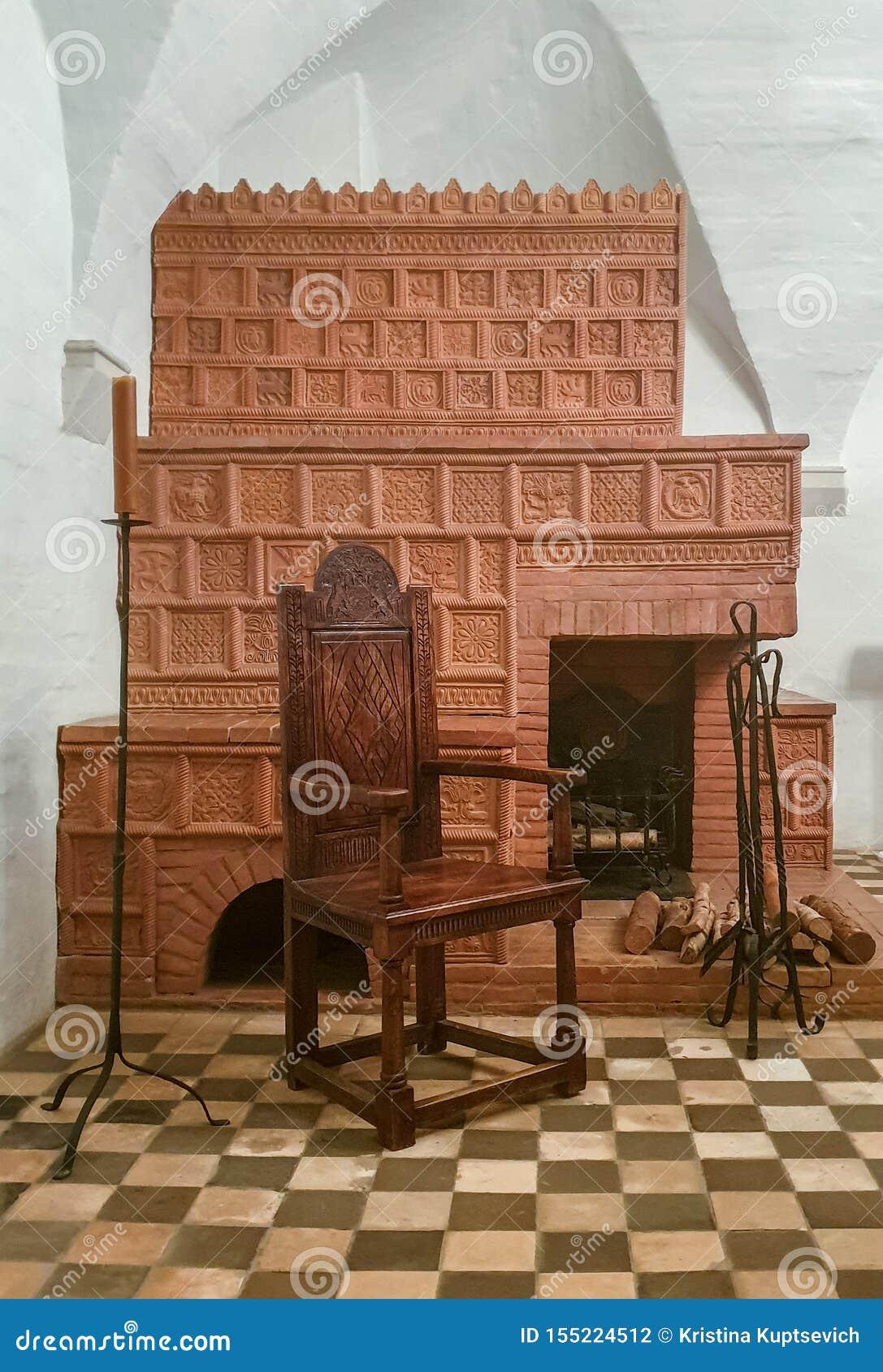 R 俄罗斯- 2019年5月12日:与一把木椅子、蜡烛和一个壁炉的地道历史中世纪内部与瓦片