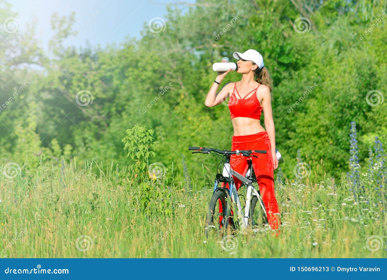 R 健身女孩在自行车附近休息户外并且喝从瓶的水 燃烧的卡路里概念