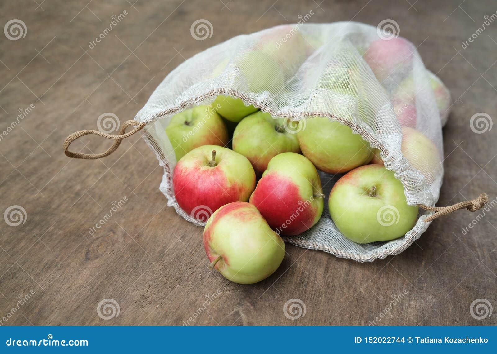 R 在可再用的滤网产物袋子的新鲜的有机苹果在木桌上