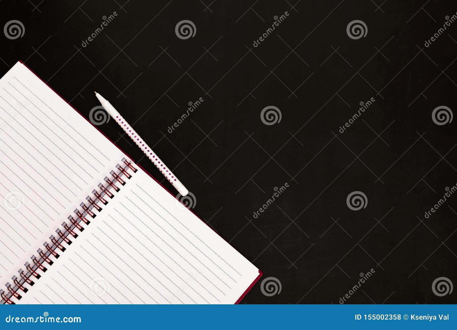 R 文具-空的开放笔记薄和笔在黑板,关闭