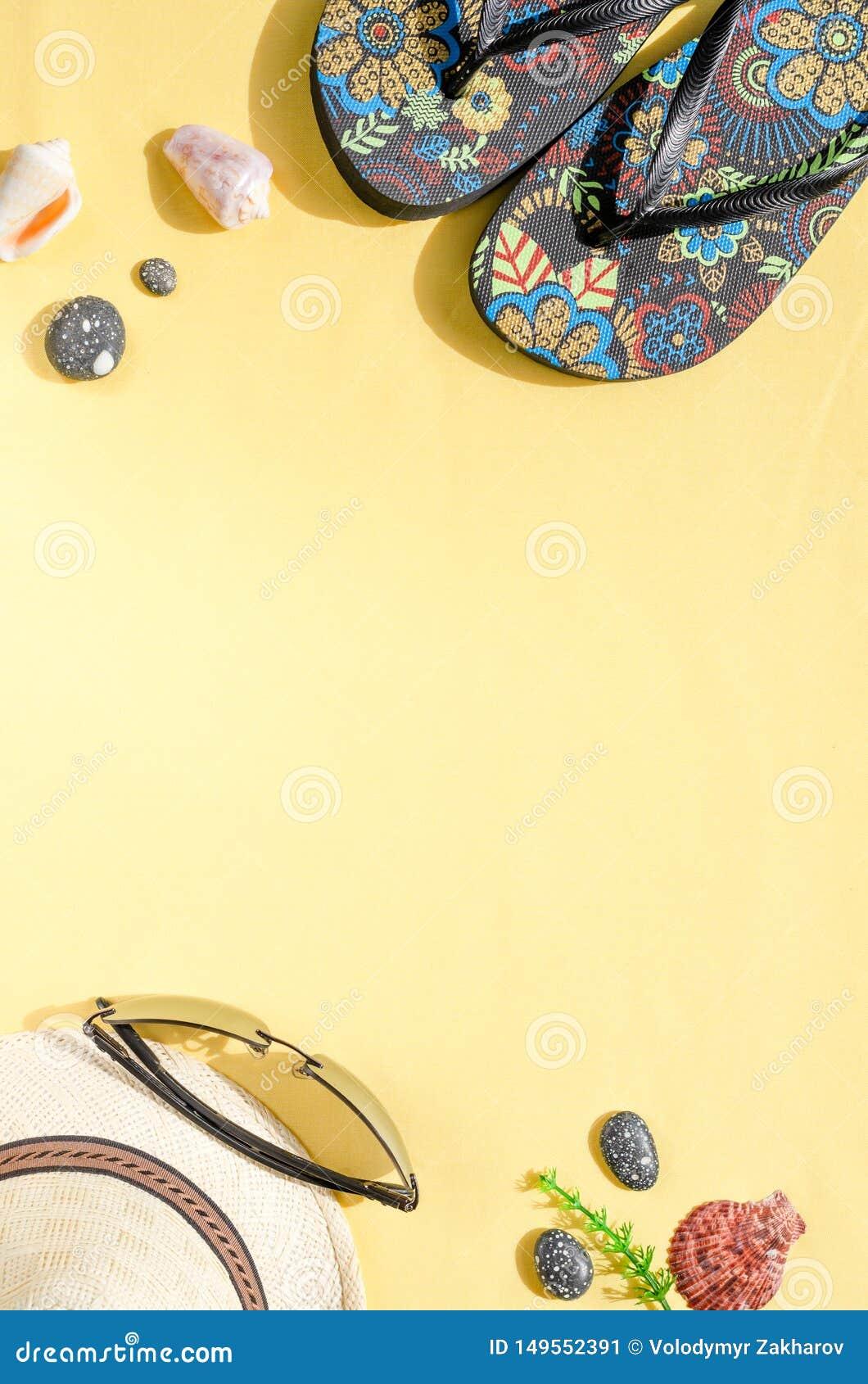 R Configuration plate de chapeau de paille, de lunettes de soleil, de bascules ?lectroniques et de coquillages sur le fond jaune