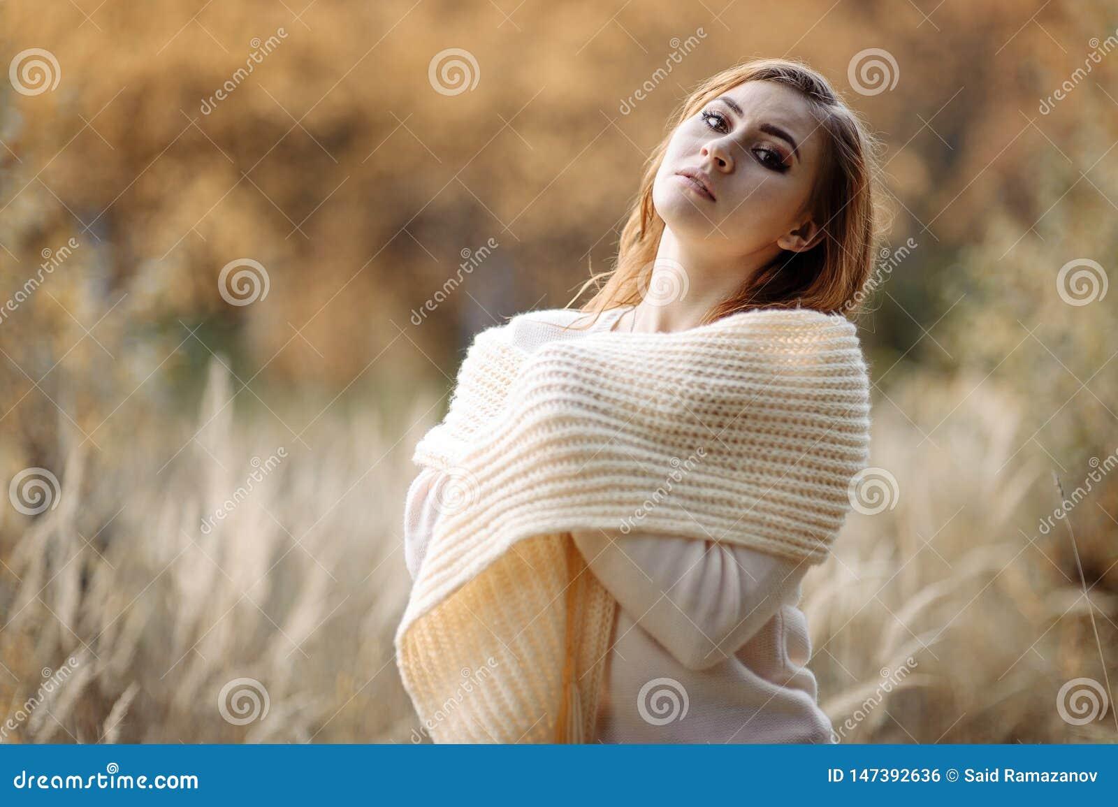 R?dh?rig flicka i ljus kl?der mot bakgrunden av h?stskogen och gula ?ron