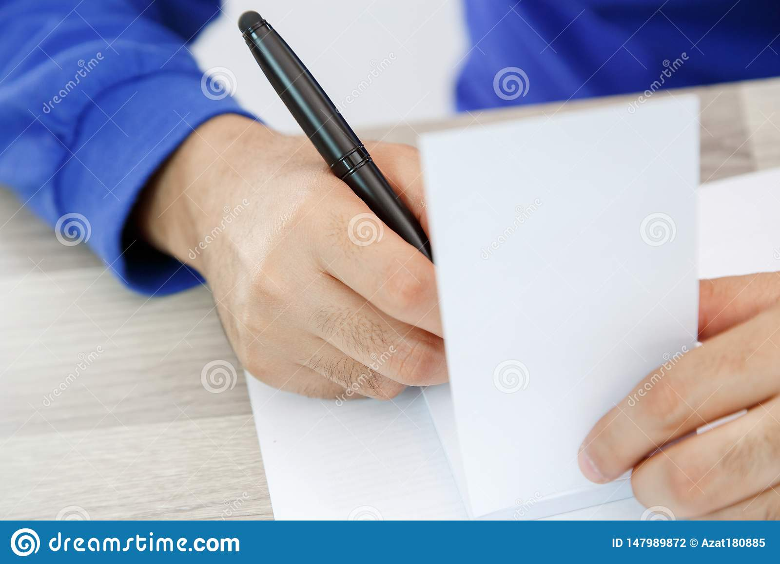 R?ki m?ody cz?owiek pisze na kawa?ek papieru