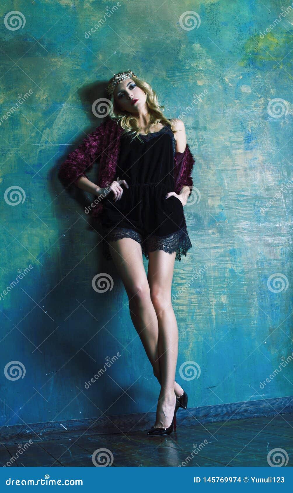 R?knar samman den b?rande kronan f?r den unga blonda kvinnan i felik lyxig inre med tomma antika ramar rikedombegrepp