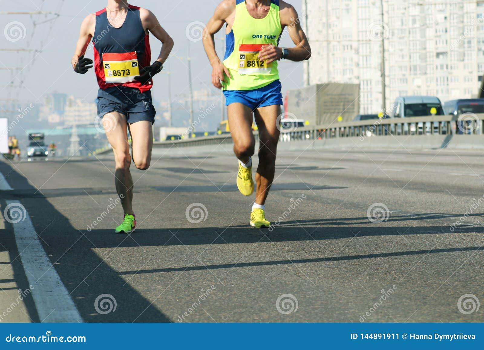 Ra?a running da maratona, p?s dos povos na estrada de cidade Grupo de corredores novos alguns medidores da chegada da maratona di