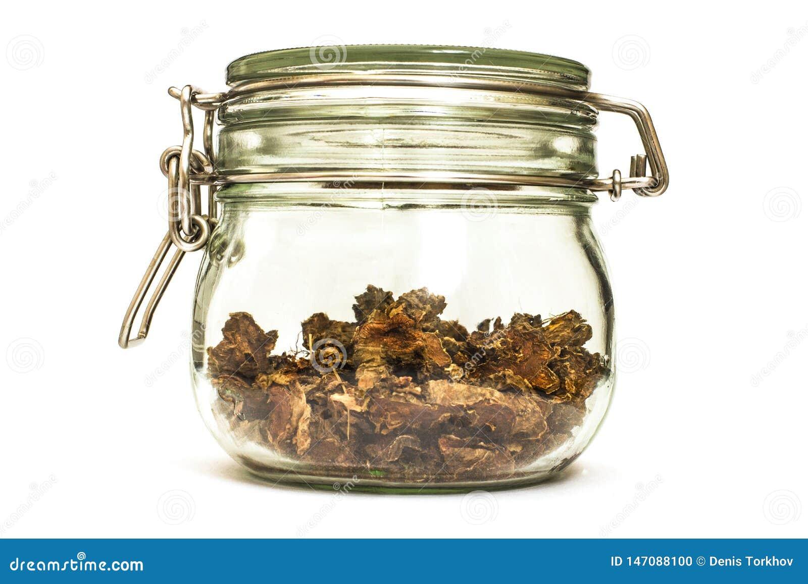 Ra?z seca cortada del rosea de Rhodiola en un tarro de cristal en fondo blanco natural