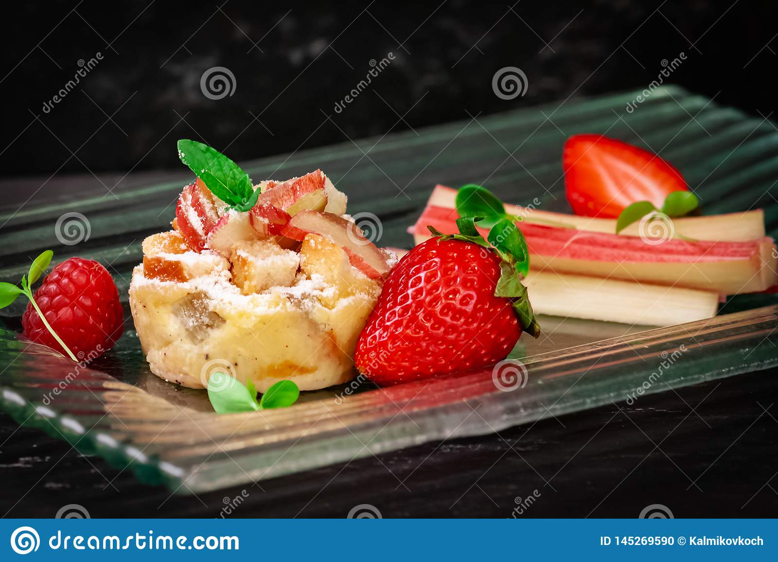 Rabarbaru tort z truskawką na szklanego talerza bocznym widoku