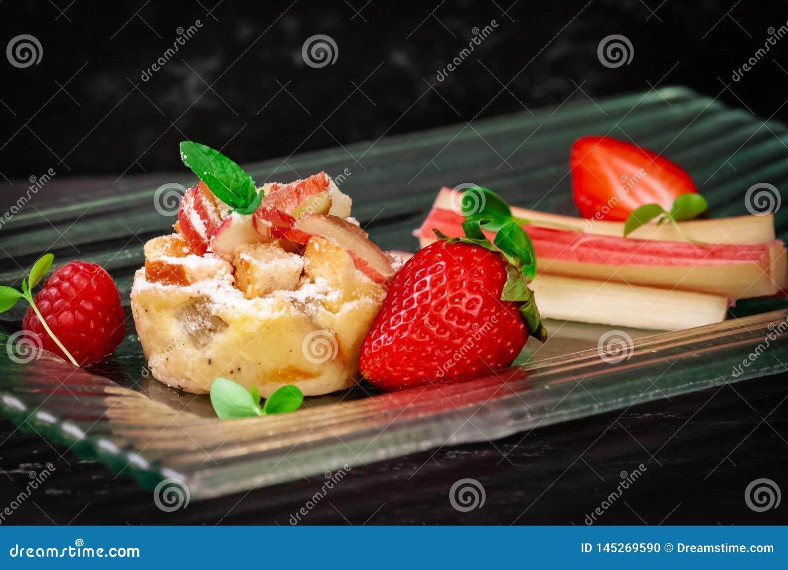 Rabarberkaka med jordgubben på sikt för sida för exponeringsglasplatta