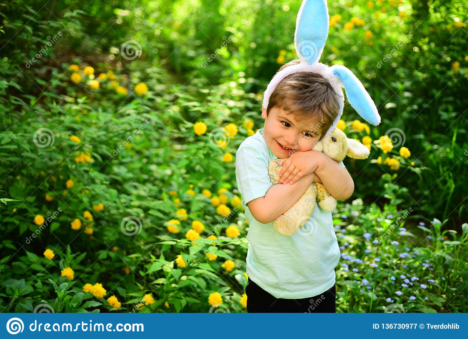 Rabbit kid with bunny ears. Hare toy. Egg hunt on spring holiday. love easter. Family holiday. Little boy child in green