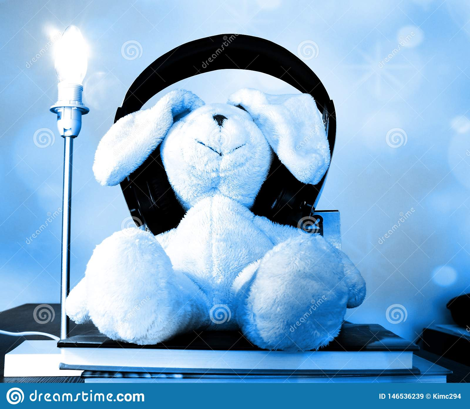 Rabbit plush toy with wireless headphones sitting on books enjoying music. Soft blue bokeh effect