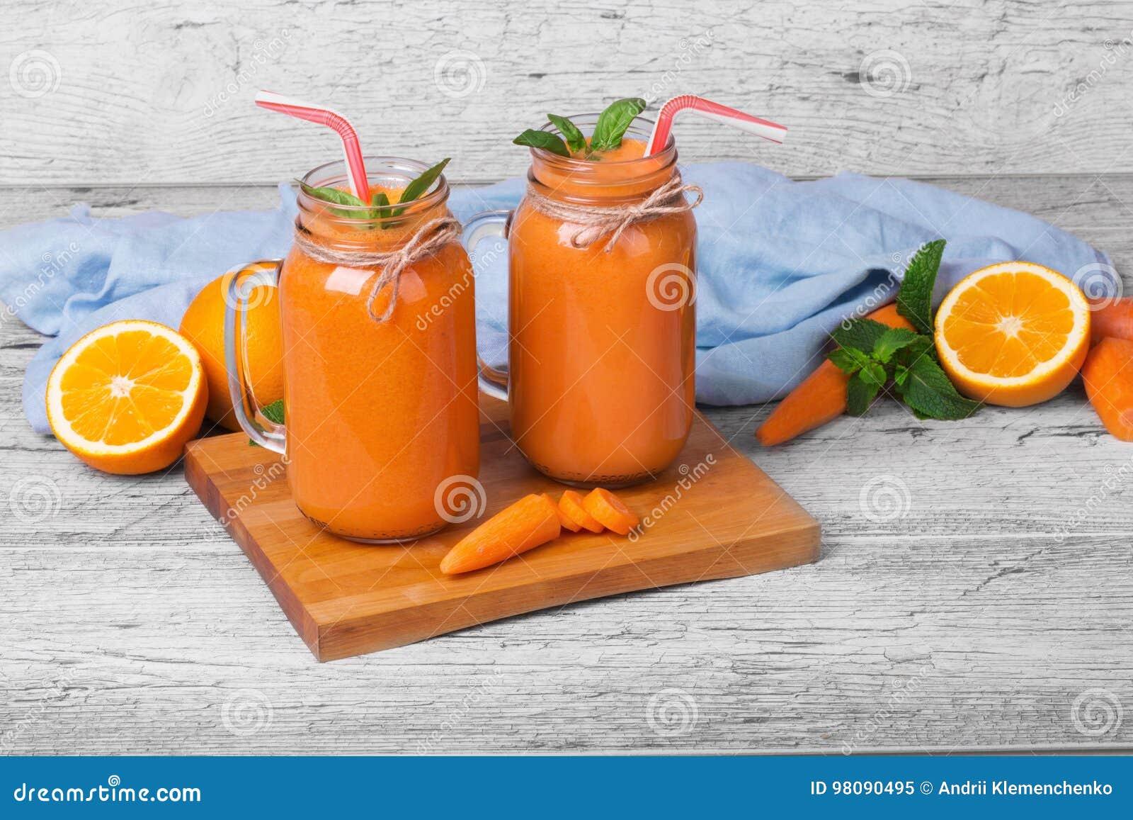 Raccord en caoutchouc et jus d orange Bouteilles de sain, organiques, smoothie de fruit sur un fond en bois Cocktail de Vegan Cop