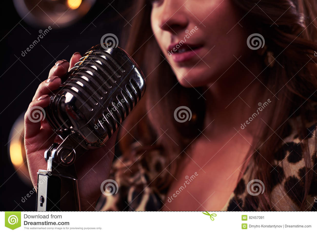 Rack focus of a girl holding a silver vintage microphone