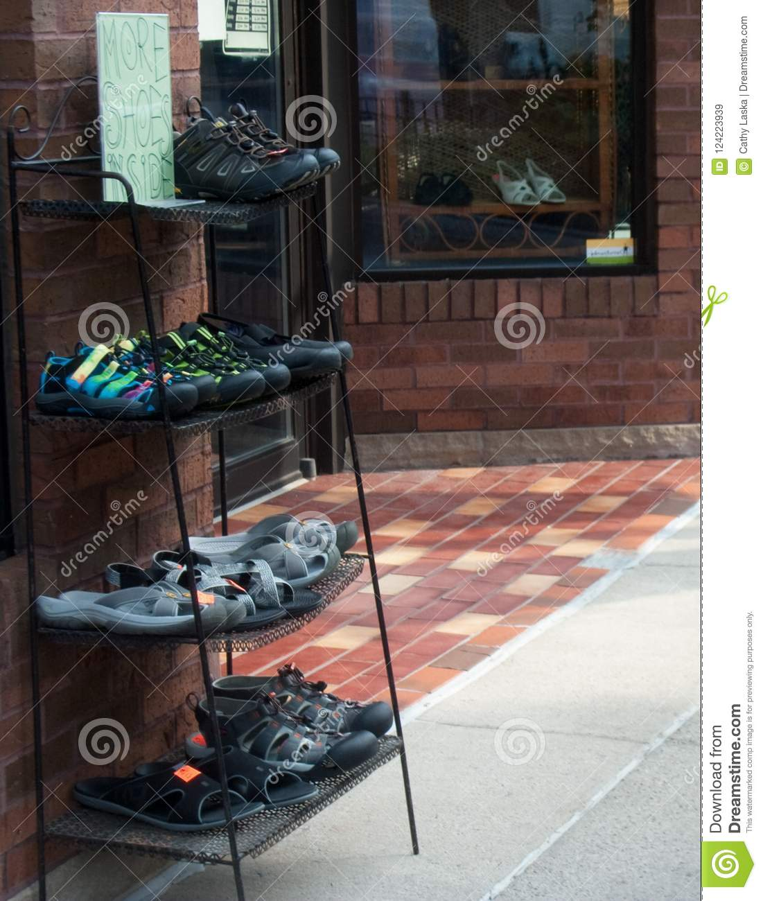 2e97c692d14 Rack of men and women shoes outside shoe store. Shoes also on rack behind  glass of store window.