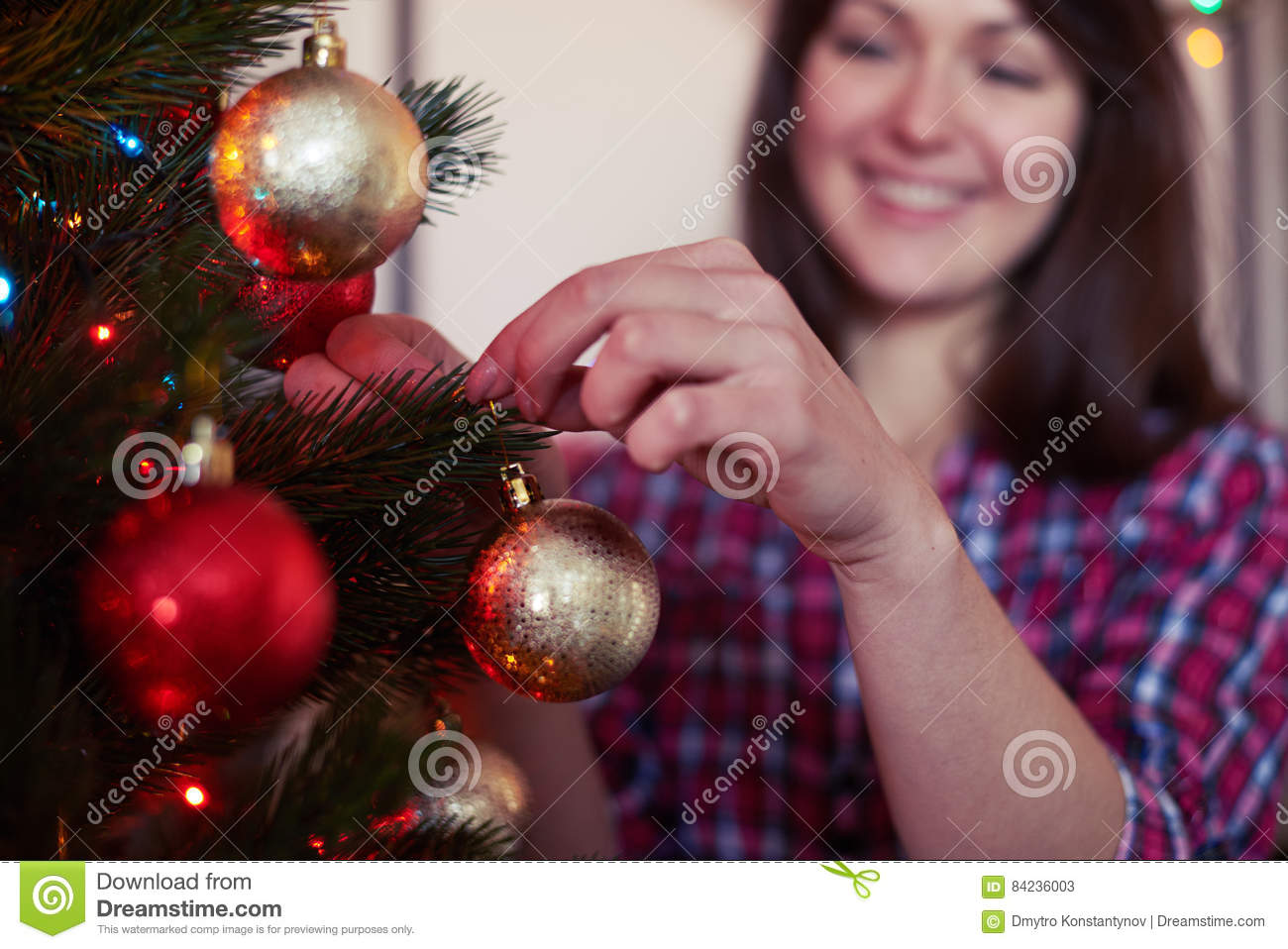Rack shot on pleased girl decorating evergreen tree with balls