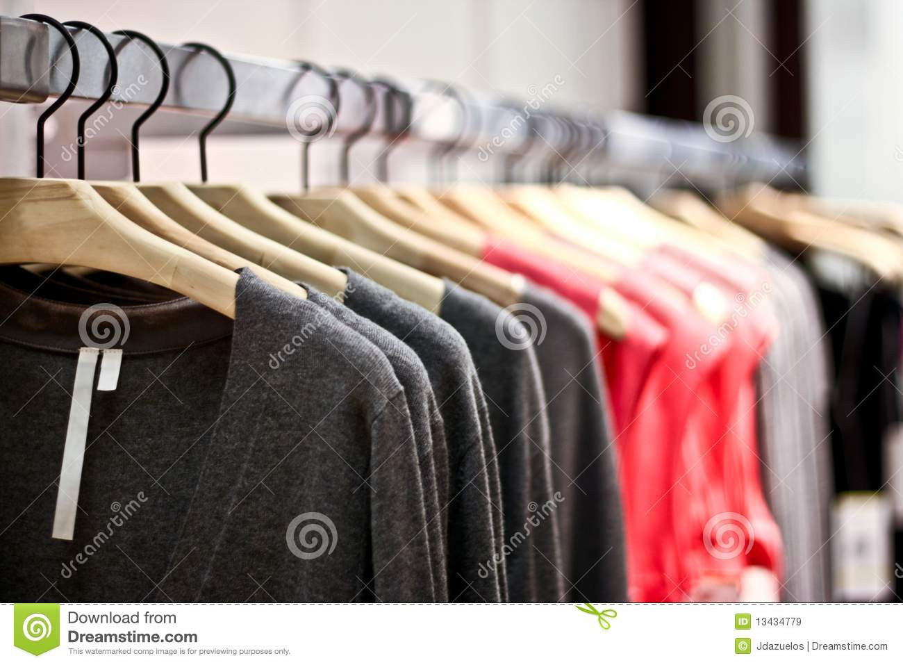 Racks Of Sweaters And Shirts Hanging In A Store Royalty